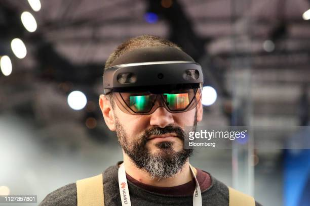 An attendee wears a Microsoft Corp HoloLens 2 headset as he uses the Bentley Systems Inc Synchro XR augmented reality app at the Microsoft Corp stand...
