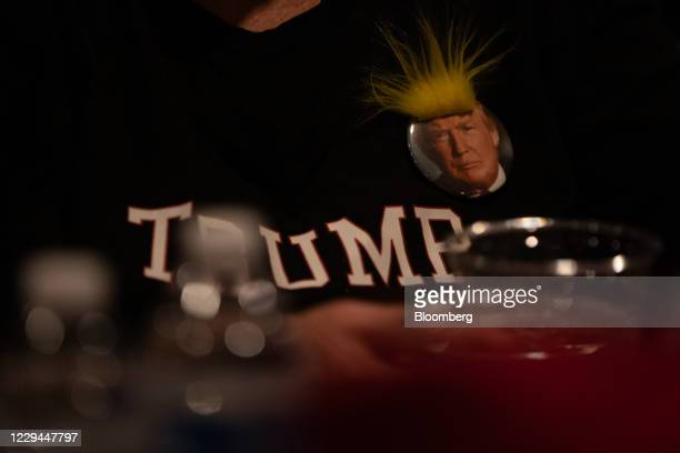 An attendee wears a pin with an image of US President Donald Trump during a 2020 US presidential election night 'Trump Re Election' watch party at...