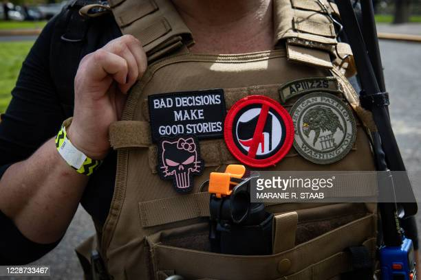 """An attendee wears a """"Three Percenter"""" patch during a Proud Boys rally at Delta Park in Portland, Oregon on September 26, 2020. - Far-right group..."""