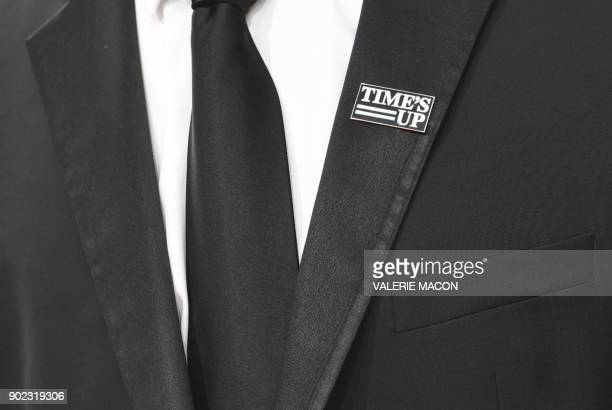TOPSHOT An attendee wears a 'Times Up' badge as he arrives for the 75th Golden Globe Awards on January 7 in Beverly Hills California / AFP PHOTO /...