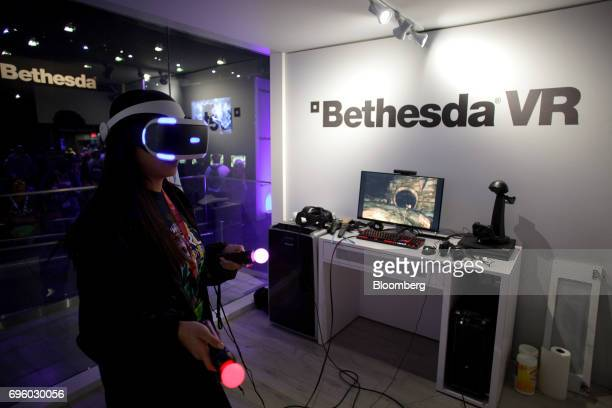 An attendee wears a virtual reality headset while playing the Bethesda Softworks LLC 'The Elder Scrolls V Skyrim' video game inside the company's VR...