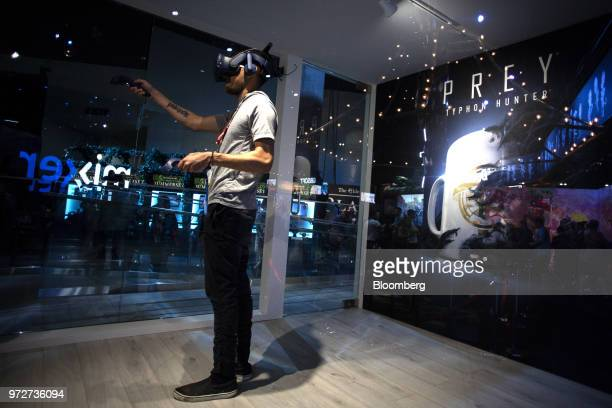 An attendee wears a virtual reality headset while playing the Bethesda Softworks LLC Prey Typhon Hunter video game inside the company's VR booth...