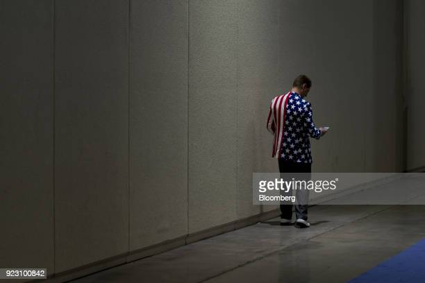 An attendee wears an American flag themed jacket while looking at his mobile phone at the Conservative Political Action Conference in National Harbor...