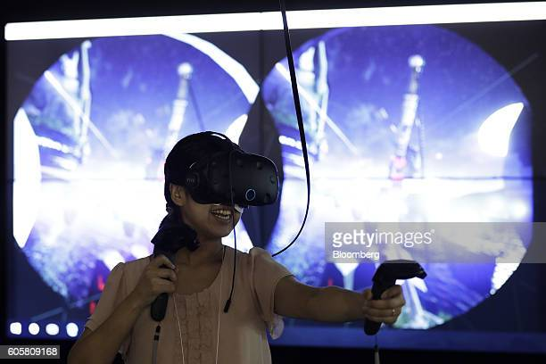 An attendee wears an HTC Corp Vive virtual reality headset to play a video game at the Tokyo Game Show 2016 at Makuhari Messe in Chiba Japan on...