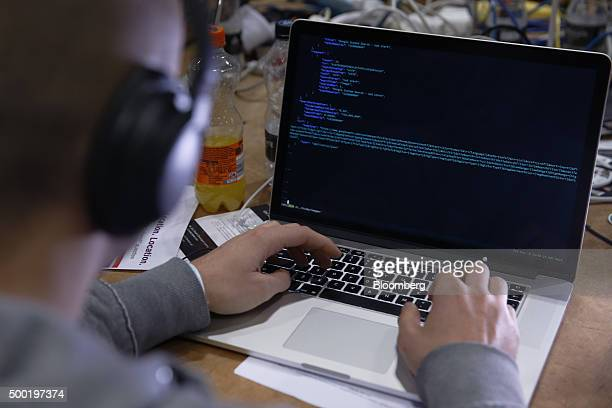 An attendee working on a Apple Inc laptop computer participates in the TechCrunch Disrupt London 2015 Hackathon in London UK on Saturday Dec 5 2015...