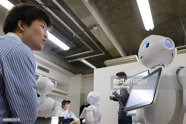 An attendee works with a humanoid robot named Pepper developed by SoftBank Corp's Aldebaran Robotics unit during a Softbank developer's workshop for...