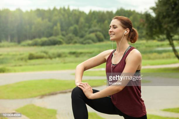 an attractive 30 year old woman doing yoga in a public park - maroon stock pictures, royalty-free photos & images