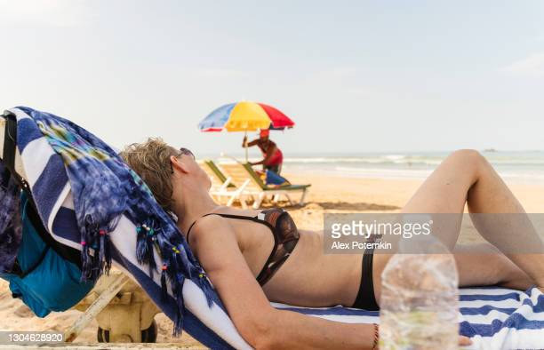 an attractive, active 50-years-old european woman, a tourist, is resting in a chaise lounge on a beach in bentota, sri lanka, when a beach worker works in the backdrop, installing a beach umbrella. - 25 29 years stock pictures, royalty-free photos & images