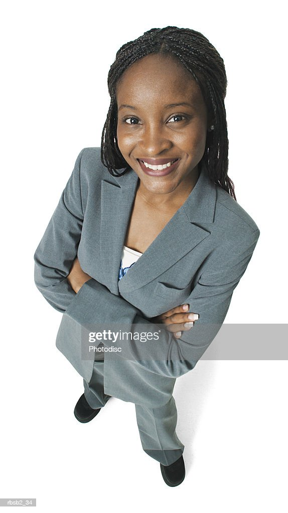 an attractive african american business woman in a grey pant suit folds her arms and smiles up at the camera : Foto de stock