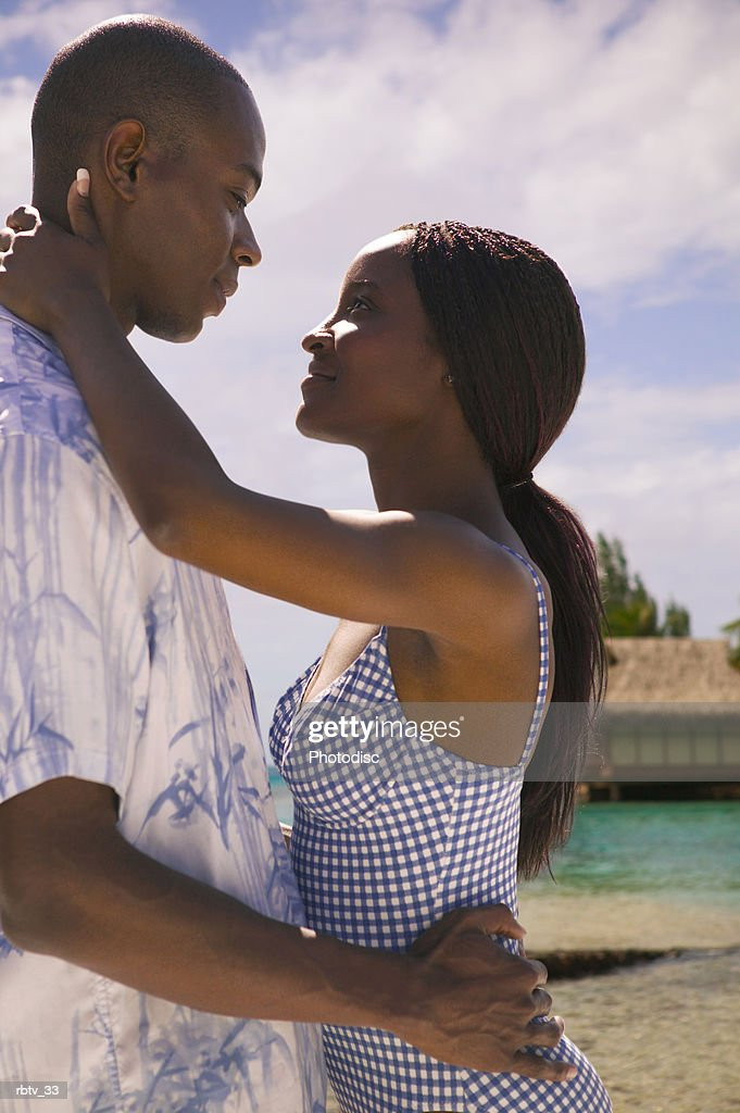 an attractive african american couple embrace at the beach while vacationing in the tropics : Foto de stock