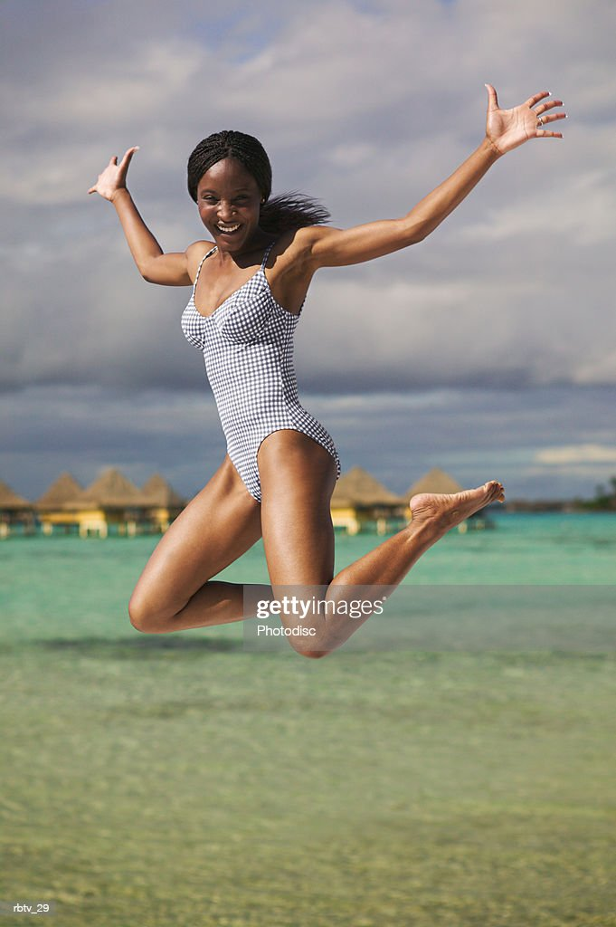 an attractive african american woman in a swimsuit jumps up into the air playfully at the beach : Foto de stock