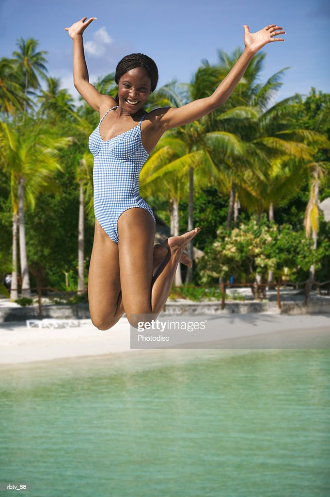 an attractive african american woman in a swimsuit jumps up playfully at the beach : Stockfoto