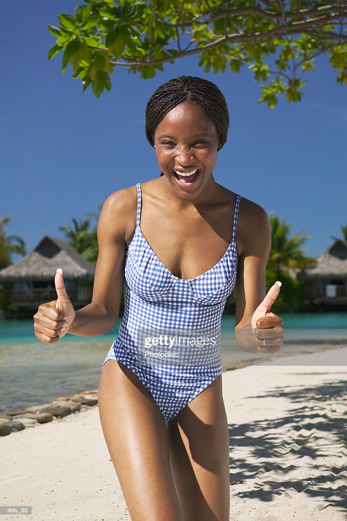 an attractive african american woman in a swimsuit smiles and gives the thumbs up as she vacations at a tropical resort : Foto de stock