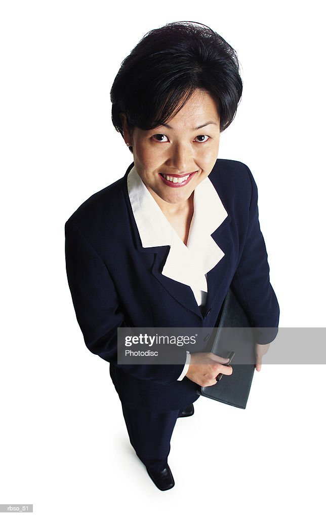 an attractive asian business woman holds a notebook and smiles as she looks up at the camera : Foto de stock