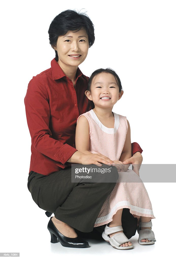 an attractive asian mother sits with her young daughter and smiles at the camera : Stockfoto