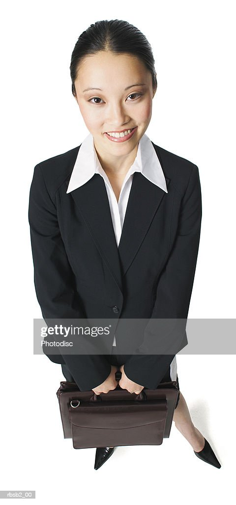 an attractive asian woman in a black business suit holds a briefcase and smiles up at the camera : Foto de stock