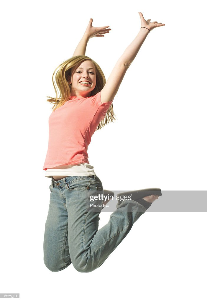 an attractive blonde female teen in jeans and a pink shirt jumps up playfully : Foto de stock