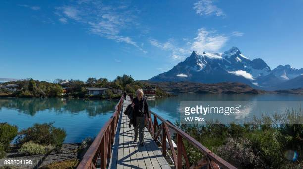 An attractive blonde female tourist about age 60 crossing the bridge from Hosteria Pehoe island to the mainland Cerro Paine Grande and Lake Pehoe are...