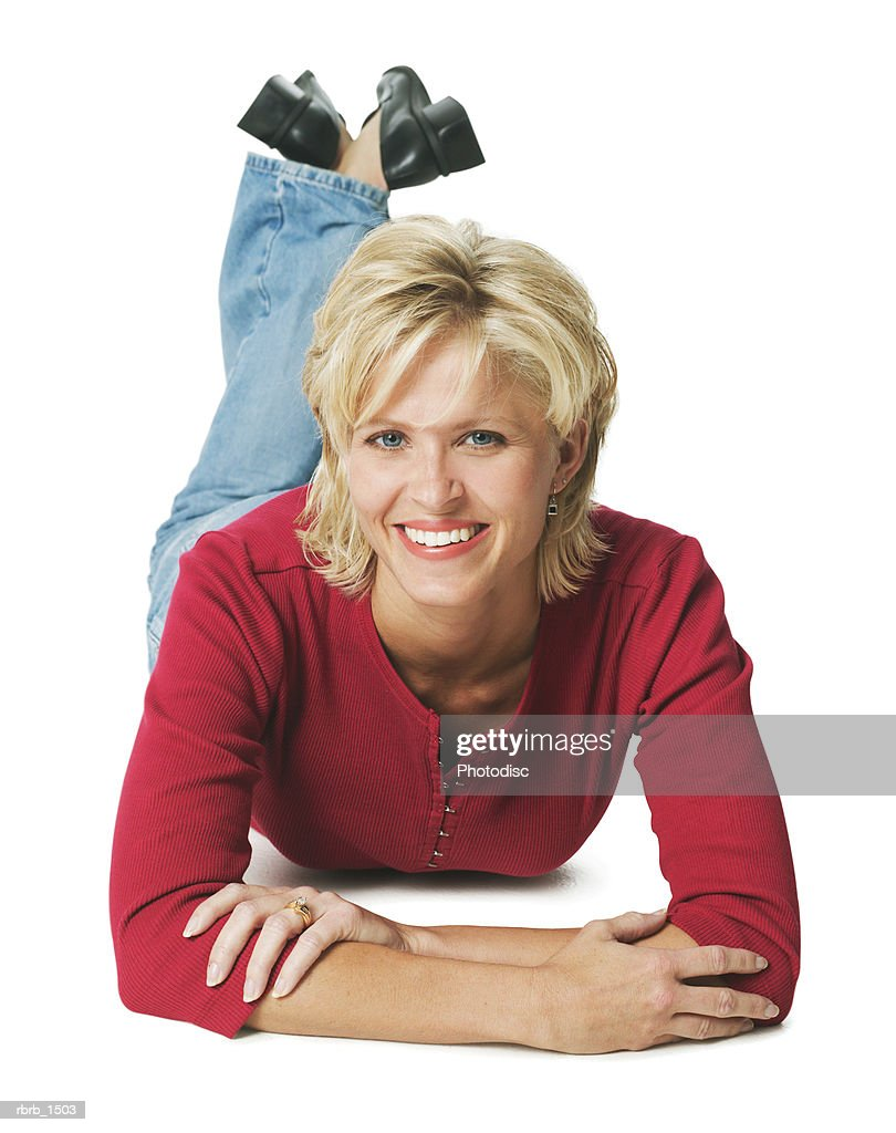 an attractive caucasian blonde woman in jeans and a red shirt lays down and smiles : Stockfoto