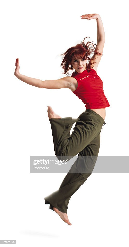 an attractive caucasian female in green pants and a red tank top hops up into the air as she throws her arms up : Foto de stock