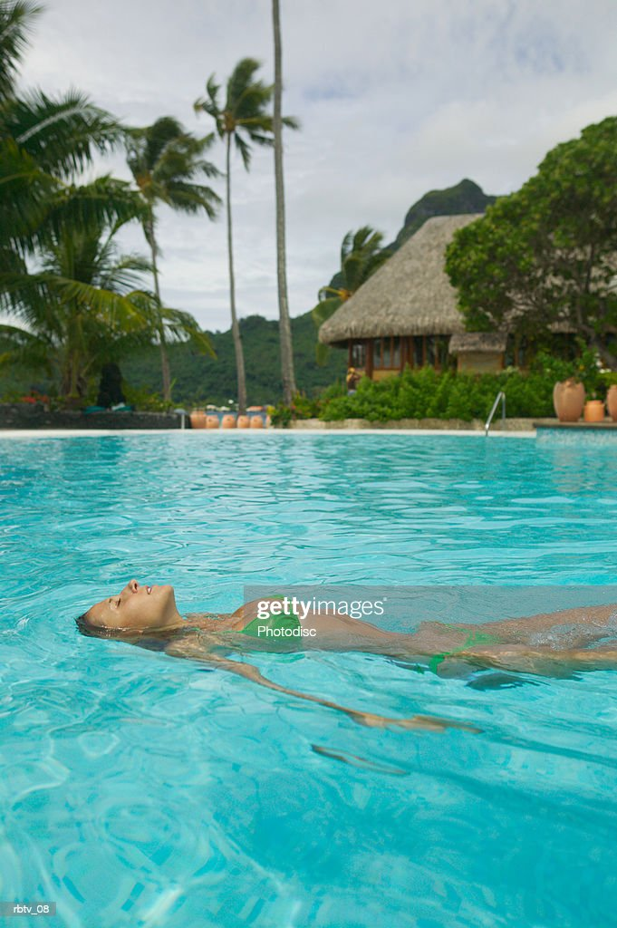 an attractive caucasian woman floats on her back in a swimming pool at a tropical resort : Foto de stock