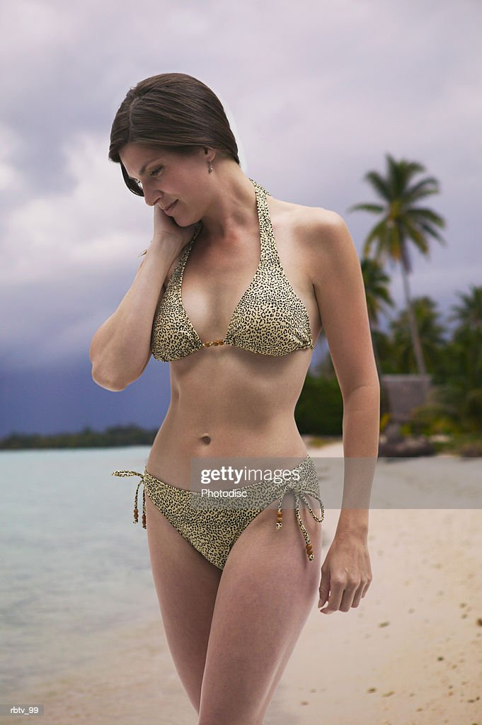 an attractive caucasian woman in a bikini strolls along a beautiful beach in a tropical setting : Foto de stock