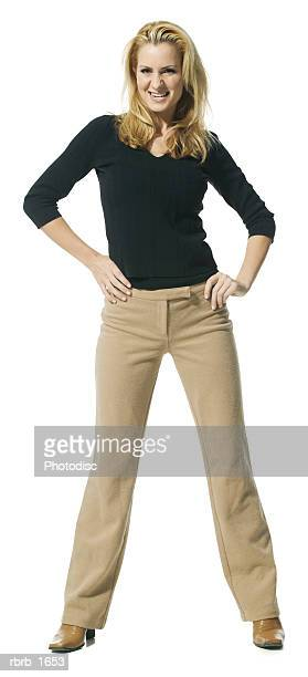 an attractive caucasian woman in tan pants and a black shirt growls angrily