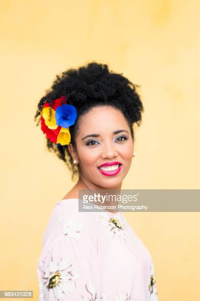 An attractive Colombian woman of African descent smiling and wearing a flower in her hair with the Colombian national colours