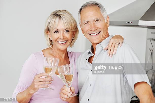 An attractive couple celebrating with champagne at kitchen