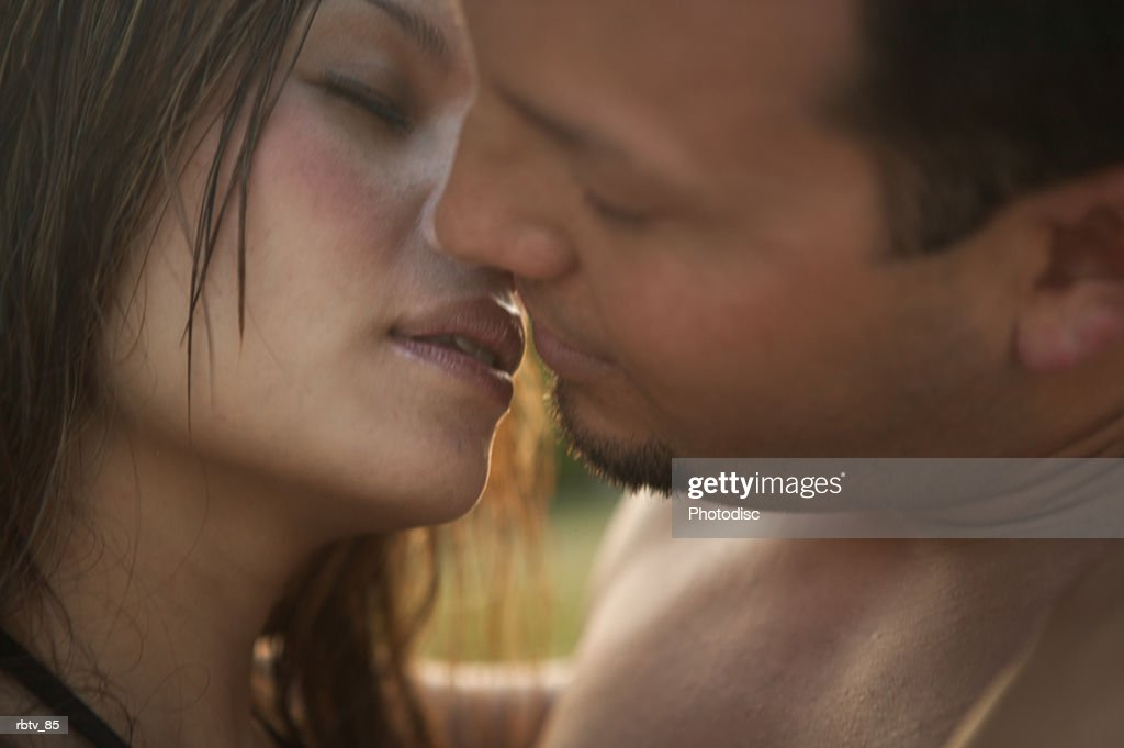 an attractive couple in swim wear lean in and kiss each other while vacationing : Foto de stock