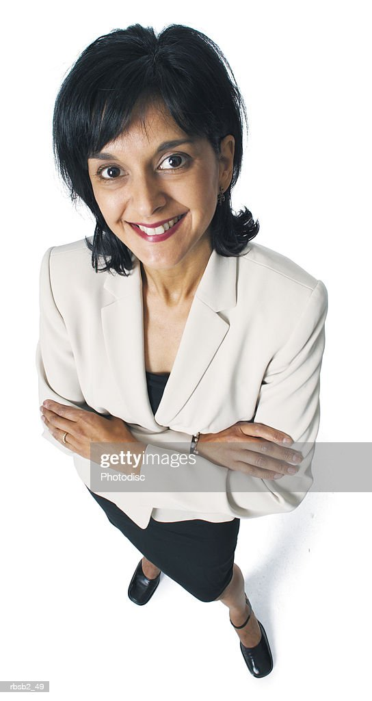 an attractive ethnic business woman folds her arms as she smiles up at the camera : Foto de stock