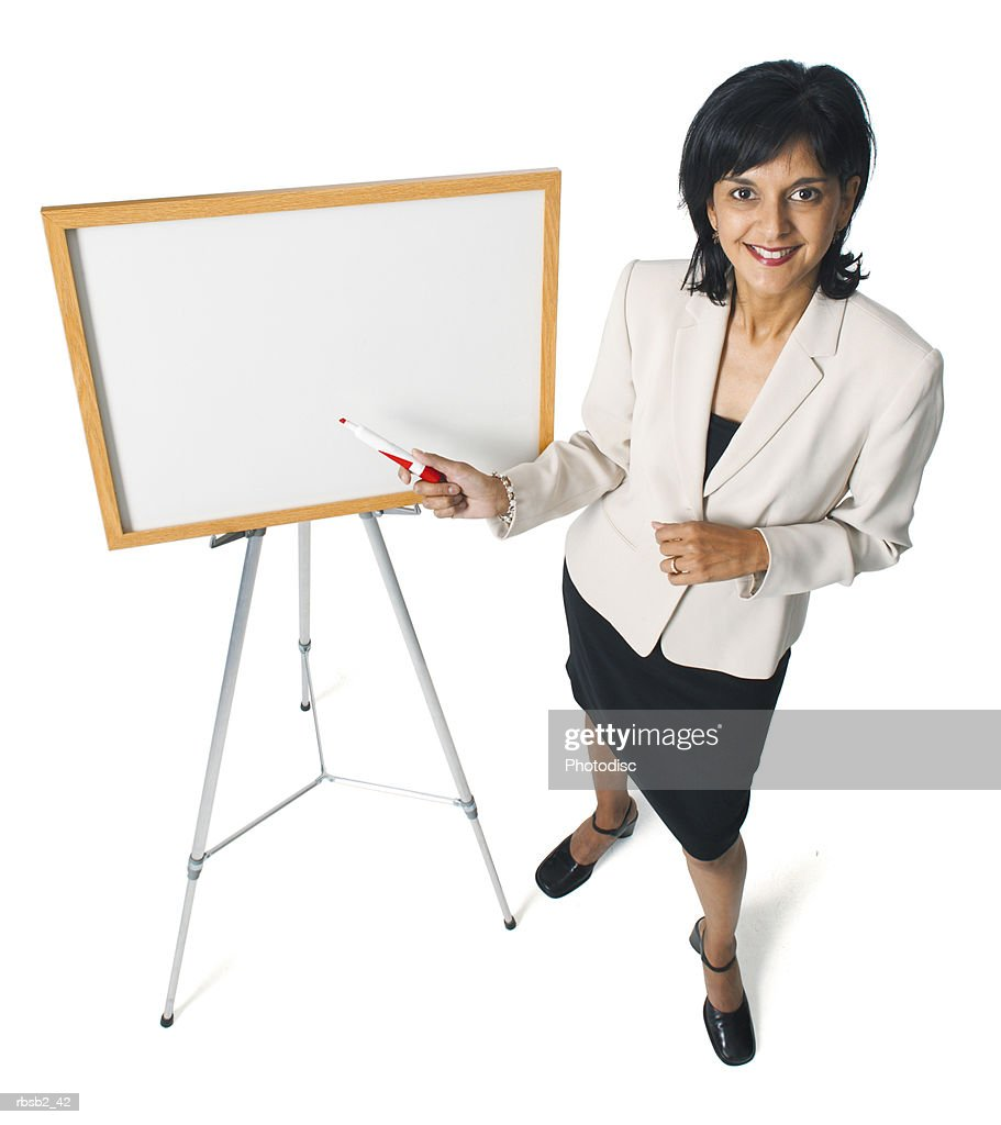 an attractive ethnic business woman points at a display board while giving a presentation : Foto de stock
