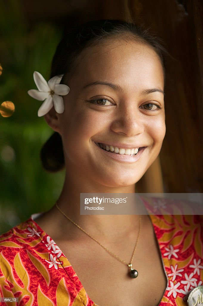 an attractive ethnic woman with a white flower in her hair smiles at the camera : Foto de stock