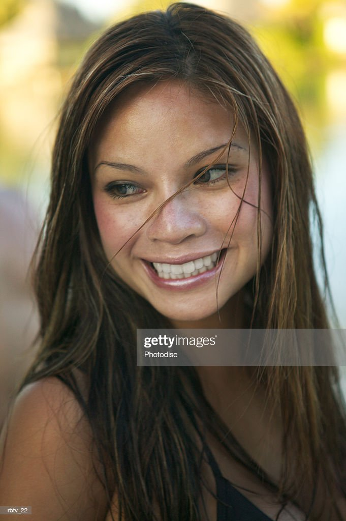 an attractive ethnic woman with long brown hair turns her head and smiles : Foto de stock