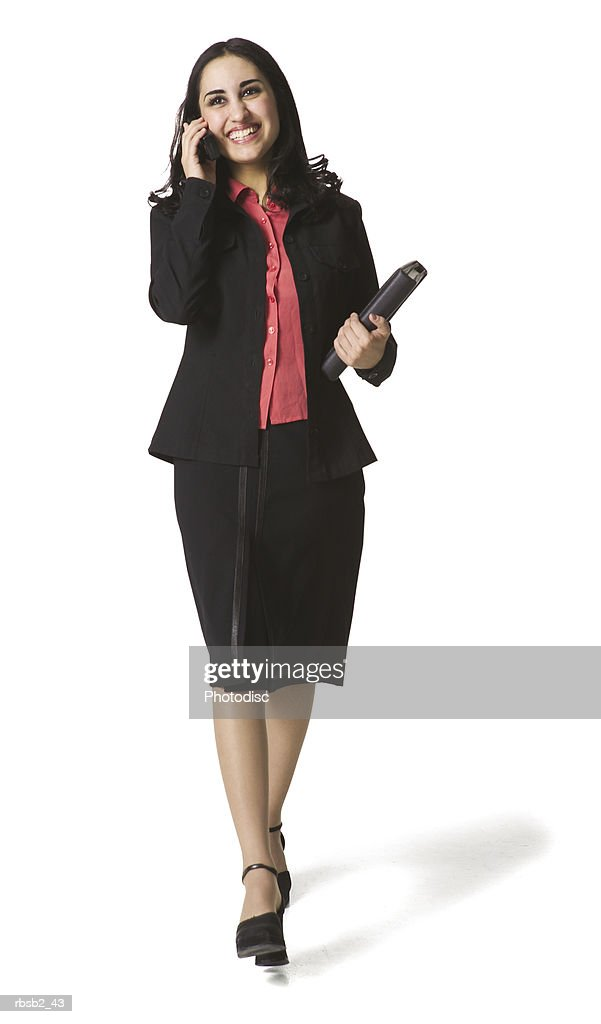 an attractive hispanic business woman walks as she talks on her cell phone : Foto de stock