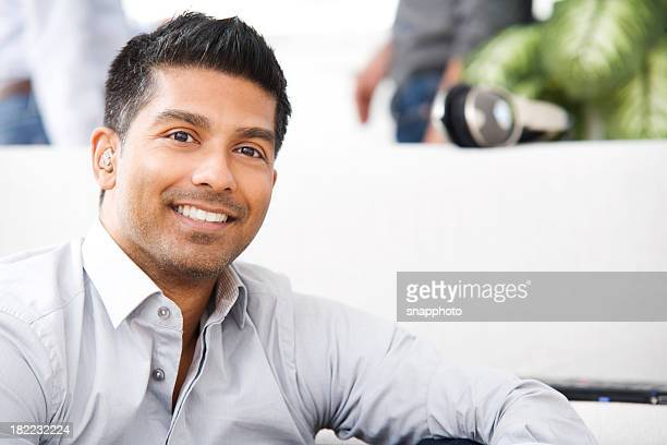 An attractive man is smiling while relaxing at home