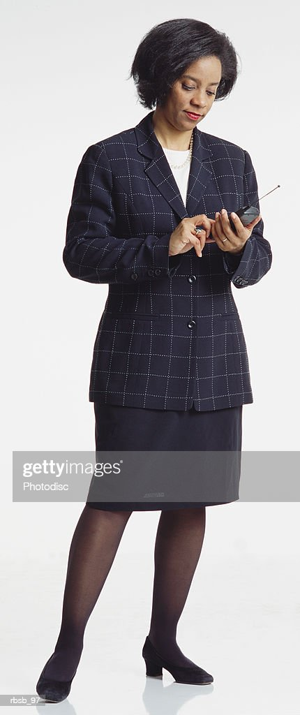 an attractive middle aged african american businesswoman with short hair dressed in a dark business suit dialing a cell phone : Foto de stock