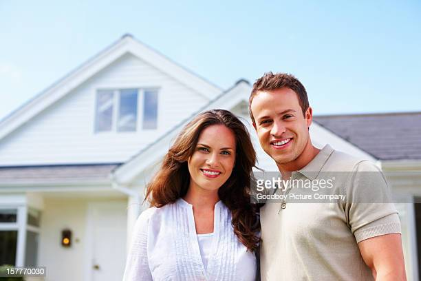 An attractive middle aged couple standing in front of house