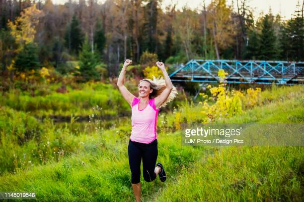 an attractive middle-aged woman wearing active wear running along a creek with her hands in the air in a city park at sunset during a warm autumn evening - human heart beating stock pictures, royalty-free photos & images