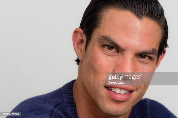 An attractive modern man in his 30s on grey background smiling at camera