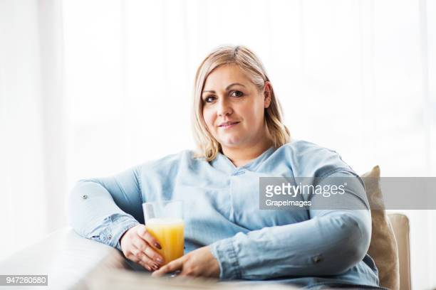 an attractive overweight woman at home, holding a glass of juice. - big fat white women stock pictures, royalty-free photos & images
