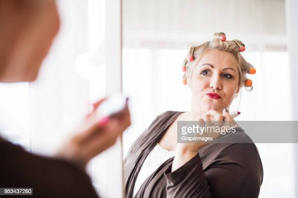 an attractive overweight woman at home, looking in the mirror and holding lipstick. - big fat white women stock pictures, royalty-free photos & images