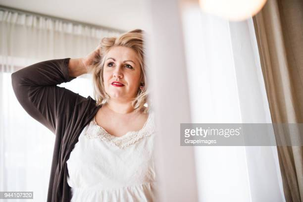an attractive overweight woman at home looking in the mirror. - big fat white women stock pictures, royalty-free photos & images