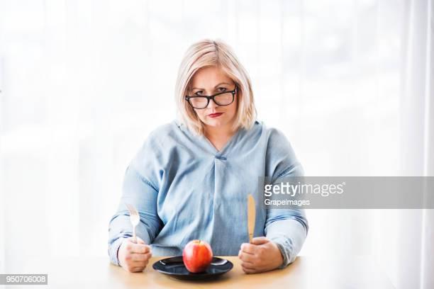 une jolie femme en surpoids à la maison, sur un régime alimentaire. - big fat white women photos et images de collection