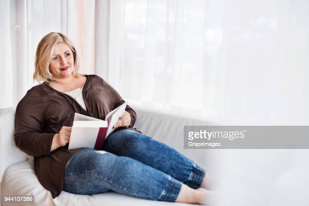 an attractive overweight woman at home, reading a book. - big fat white women stock pictures, royalty-free photos & images