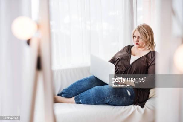 eine attraktive übergewichtige frau zu hause, mit laptop. - blond mollig frau stock-fotos und bilder