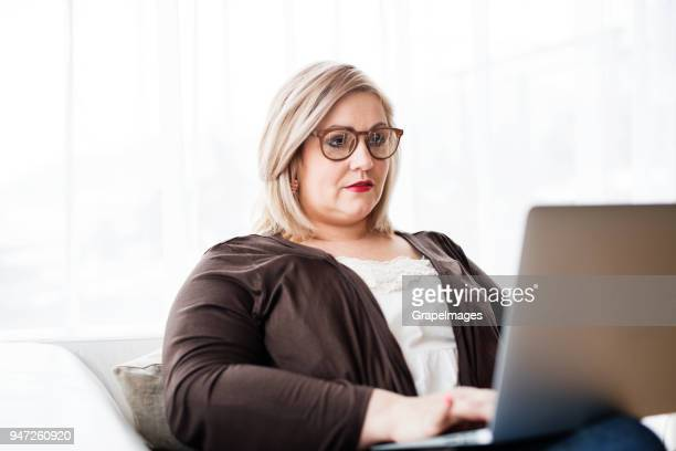 an attractive overweight woman at home, using laptop. - big fat white women stock pictures, royalty-free photos & images