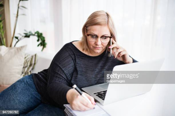 an attractive overweight woman at home, using smartphone and laptop. - fat blonde women stock pictures, royalty-free photos & images