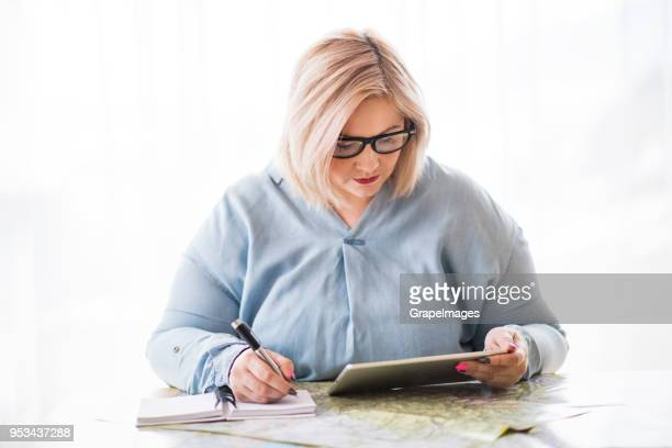 an attractive overweight woman with a tablet at home, sitting at the table, planning a trip. - big fat white women stock pictures, royalty-free photos & images