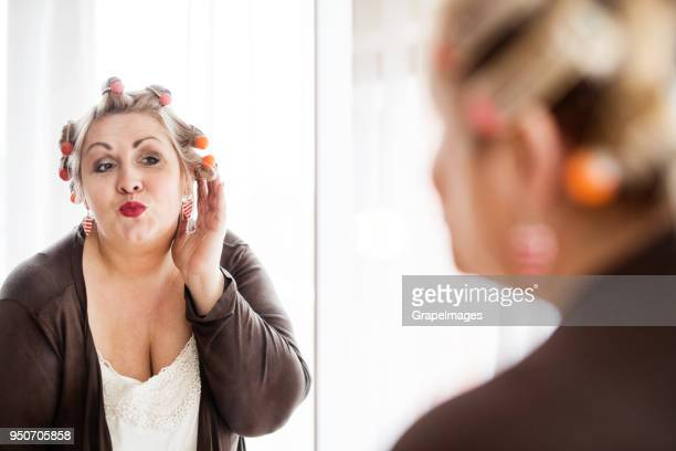 an attractive overweight woman with hair curlers looking in the mirror at home. - big fat white women stock pictures, royalty-free photos & images